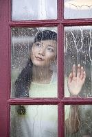 雨がつたう窓越しに外を眺める女性