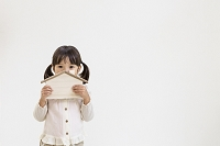 木の家の飾りを持つ日本人の女の子
