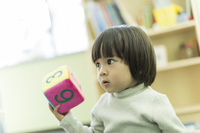 幼児教室でサイコロを持つ日本人の子供