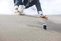 スマートフォンに飛びつくビジネスマン