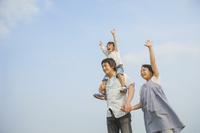 青空の下に立つ日本人家族