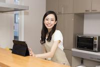 タブレットでレシピを見ながら料理をする日本人女性