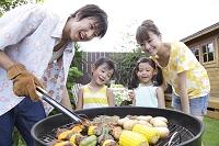 庭でバーベキューをする家族