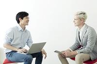 椅子に座り向かい合う20代の日本人男性と外国人男性