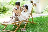 庭で本を見ている中高年夫婦