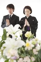 喪服姿で合掌する夫婦と祭壇の花