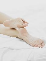 寝転ぶ女性の足の裏