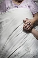 眠るシニアと若い女性の手