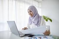 パソコンを操作するムスリムの女性