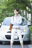 車の前で腕組みをするビジネス女性