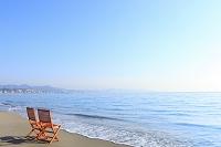 神奈川県 波打ち際の砂浜に置かれた椅子と青空