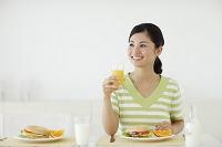 オレンジジュースを飲む女性