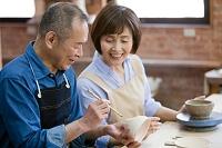 茶碗に絵を描くシニア夫婦