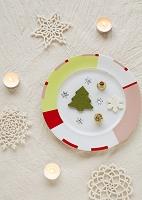 皿の上のクリスマス飾りと白いキャンドル