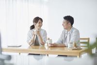テーブルで話をする日本人の若い夫婦
