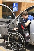 車から車いすに乗り換える男性