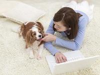 パソコンに向かう日本人女性と犬