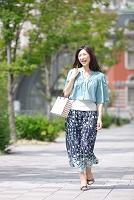 買い物袋を持って歩く中高年日本人女性