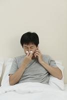 鼻をかみながら電話をかける日本人男性