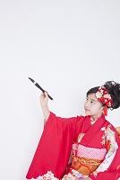 振り袖姿で筆を持つ女児