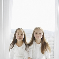 窓辺で微笑む姉妹
