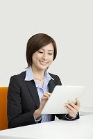 タブレットを笑顔で操作するビジネスウーマン