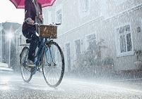 雨の中自転車で傘を持って走行する