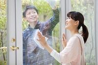 窓拭きをする夫婦