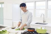 エプロンをして料理をする中年男性