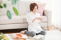 リビングでスマートフォンを操作する日本人女性