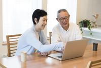 ノートパソコンを操作する日本人シニア夫婦