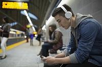 地下鉄のホームで音楽を聴く男性