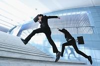 階段をかけあがる日本人ビジネスマン