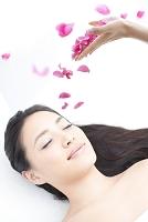 仰向けに横になっている日本人女性とバラの花びら