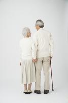 ステッキを持って寄り添う老夫婦後姿