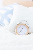 ベッドの上に置かれた目覚まし時計