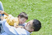 芝生の上で遊ぶ日本人親子
