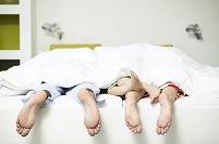 ベッドから足がのぞいている家族