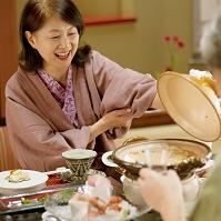旅館で土鍋のふたを開けるシニア日本人女性