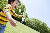 公園で模型飛行機を持って走る日本人の男の子