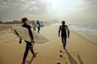 友人とサーフィンする若者