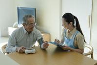 血圧を測るシニアの男性