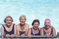 笑顔でプールに入るシニア外国人女性