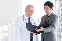 医師に書類を見せるビジネスマン