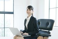 膝の上でパソコンを操作するスーツ姿の若い女性