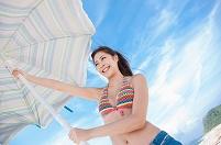パラソルを広げる水着姿の日本人女性