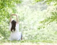 新緑の中で伸びをする日本人女性の後ろ姿