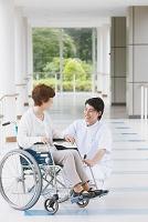 廊下で会話する車椅子のシニア女性と若い男性看護師