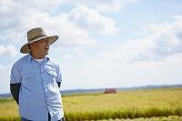 秋の田園に立つ農夫