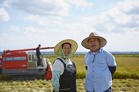 秋の田園に立つ農家の夫婦